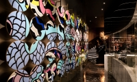The feature wall within Cantonese restaurant YEN, embellished with custom-designed enamelled discs forming a dragon motif; the result of working with local craftsmen practicing a centuries-old craft.