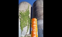 """At the site of industrial silos, four beacon sets made from locally sourced oil barrels narrate the bayous history, community, ecology and feature engagement activities. (image: stacked barrels spell out """"history"""")"""