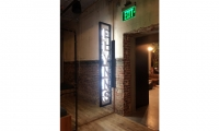 Twitch needed an entry sign for their employee video game lounge, named after the Tron arcade. The design nods to the original movie's neon sign without recreating it.