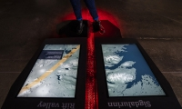 This presence-sensing installation tells the geological story of Þingvellir and how it was formed. It is composed of an interactive floor, presence sensing and 3D animation. (image: person standing over digital projection of lava and mountains)