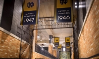 Banners hung in the players' tunnel honoring all 11 National Championships. The iconic 'Touchdown Jesus' mural can be seen in the back beyond the gate. (image: banners hanging in grand hallway)