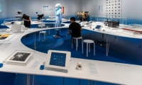 A single, meandering surface, the table seamlessly carries audio and video stations, plexiglass cases, reproductions, object labels, interactive objects, and silica gaskets for microclimate control.