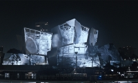 A still image taken during the performance showing an architectural manipulation. (image: design projected on concert hall exterior)