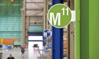 Like street signs, markers bearing alphanumeric locations within the factory grid project from the steel columns supporting the building. Each production bay is designated a different color for ease of navigation.