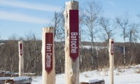 The trade route playground is a three-dimensional scaled map, with trading posts and Métis communities identified by large upright log markers.