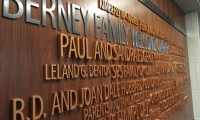 The wall design features a sculptural rendition of a visual word cloud, with the scale of each name relative to the size of each contribution.