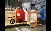 """The low-tech """"Share Your Ideas"""" space invites visitors to record their comments about global warming on recycled """"make-readies"""" used to test ink coverage in offset printing."""
