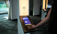 Digital displays combine with natural material choices like bronze.