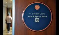 Circular stateroom corridor signs use quadrant color-coding and symbols to help guests navigate to the ship's venues.