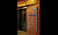 The etched-glass elevator directories measure 1700mm high by 750mm wide. Information is displayed hierarchically, with the lobby name and deck number at top, the ship's deck plan, a You Are Here indicator, and a directory of the ship's offerings by deck level.