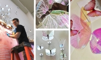 """Three-dimensional, iridescent acrylite butterflies """"fly free"""" above the glass wall right out into the lobby! As the viewer changes position, the wings change color as though fluttering."""