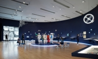 LED strips in the baseboards along the curvature of the gallery, enhanced the feeling of a planetary horizon and the hanging models floated against the midnight blue of the walls.