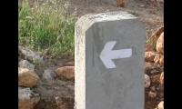 Small directional signs bear simple arrows directing visitors to the ancient towns.
