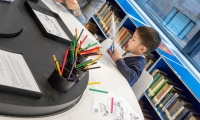 In the library, an analog activity table provides engagement for even the youngest visitors. (image: young child coloring)