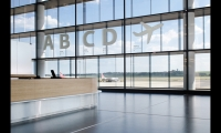 On the terminal's glass façade, oversized 1.5-meter-high letters in Fedra Sans indicate gates. Designers created a blurred effect with the letters, which were digitally printed with pixelated white on transparent vinyl.