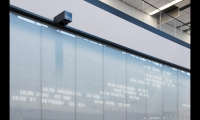 A 40-meter-long, 4.5-meter-high arrivals display functions almost as public art. Arrivals are indicated on white LED panels behind an existing glass wall covered in translucent white vinyl.
