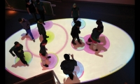 In an area where traffic tends to slow while visitors are waiting for the next experience, an interactive floor installation by media artist Scott Snibbe encourages social interaction by generating colored circles in response to visitors' movements.