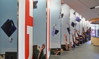"""Below the mural, a """"sawtooth"""" wall welcomes students with one of KIPP NYC's motivational phrases, """"Go. Graduate."""" (Photo: Garrett Rowland)"""