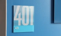 Room identification signs are lenticular displays featuring the room number at one angle...