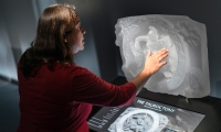 Temple artifacts are rendered in translucent resin and set atop interactive displays that offer a deeper dive into content and scholarship.