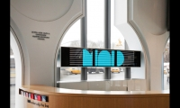 The attractor display is also visible from the interior, acting as a graphic backdrop for the information desk.