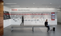 Branded corporate history exhibitions for SanDisk's headquarters are limited to customer-facing areas, while direct branding is minimized in workspaces.