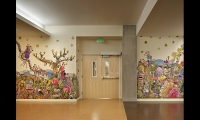 Kittenchops' whimsical, colorful mural enlivens bland hallways and engages patients and visitors.