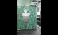 For restrooms, Scher designed super-scaled symbols in metal applied to tile walls.