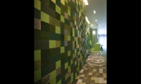 In a party room, a graphic, pixel-inspired textile composition of varying shades of green is a contemporary translation of the lush, great outdoors.