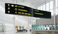Toronto Pearson International Airport: Overhead signs are designed in a double-curved propeller shape that blends with the 'airplane wing' roof structure.