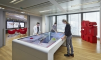 A large multi-touch interactive table allows visitors to collaboratively explore product requirements.