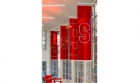 Plexiglas banners in the school colors highlight the large windows and cast a red glow across the space.