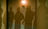 Silhouette projections of the Privy Council members, their names listed on the walls in cut-vinyl film, convey the intimidating scene of Victoria's first day as queen.