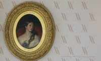 Monogrammed wallpaper provides the backdrop for Albert's favorite portrait of Queen Victoria.