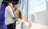 A pressure-sensitive football in a cast of each players hand that visitors touch to activate a screen above that plays a short video of the player's career highlight and stats.