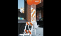 They repurposed striped barriers into signage by adding vinyl lettering, balloons, and oversized posters.