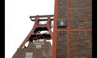 Zeche Zollverein's iconic winding tower looms over the site. Buildings are identified with a letter designation (corresponding to one of three districts), a number, and their historic German names.