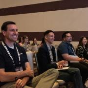 Conference audience listening to Evan Voyles, Neon Jungle, speak.