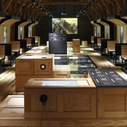 An exhibition as a virtual journey through time and space, experienced through the interaction of multimedia, graphics and authentic objects. (image: exhibition space with many wooden boxes)