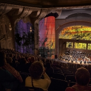 PR photo: The design team needed to convey the scale of the projection, audience immersion and that animation+symphony doesn't necessarily equate to Fantasia's dancing hippos. (image: colorful projection mapping in theater)