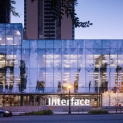 Interface Inc.'s new headquarters features a complex photomosaic façade – a pixelated image of a forest scene comprised of 307 panels sheathed in recyclable polyester. (Night)