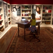 Visitors sit at the desk and immerse themselves in the stories of three homegrown Mississippi writers. Paired with sound design, the typewriter's keyboard is highlighted as words projected on paper. (image: girl sits at desk)