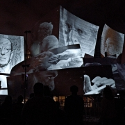 A still image taken during the performance of a moment which paid homage to past influential figures of the LA Phil. (image: design projected on concert hall exterior)