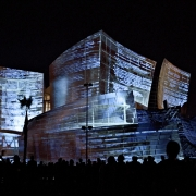 A still image taken during the performance displaying the files in the archive and some of the algorithms used to process them. (image: design projected on concert hall exterior)
