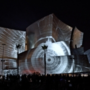 A still image taken during the performance of a moment in which the viewer is moving through the LA Phil's performance history. (image: design projected on concert hall exterior)