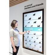 Gensler designed a digital donor recognition in addition. (image: woman interacts with wall screen)