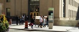 Steer Header Image - Sign on a sidewalk with people walking