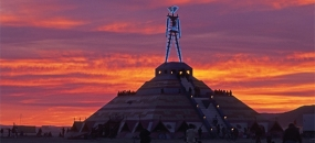 Photo of the Burning Man efigy on top of a pyramid in the Desert