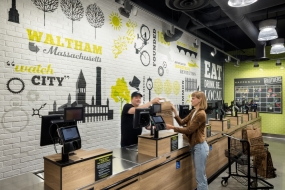 Brothers Marketplace Waltham Wins at the 2019 design:retail Spectrum Awards (image: woman checks out at store)